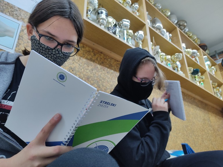 Two girls writing into their copy of Shooting Notes and setting goals.
