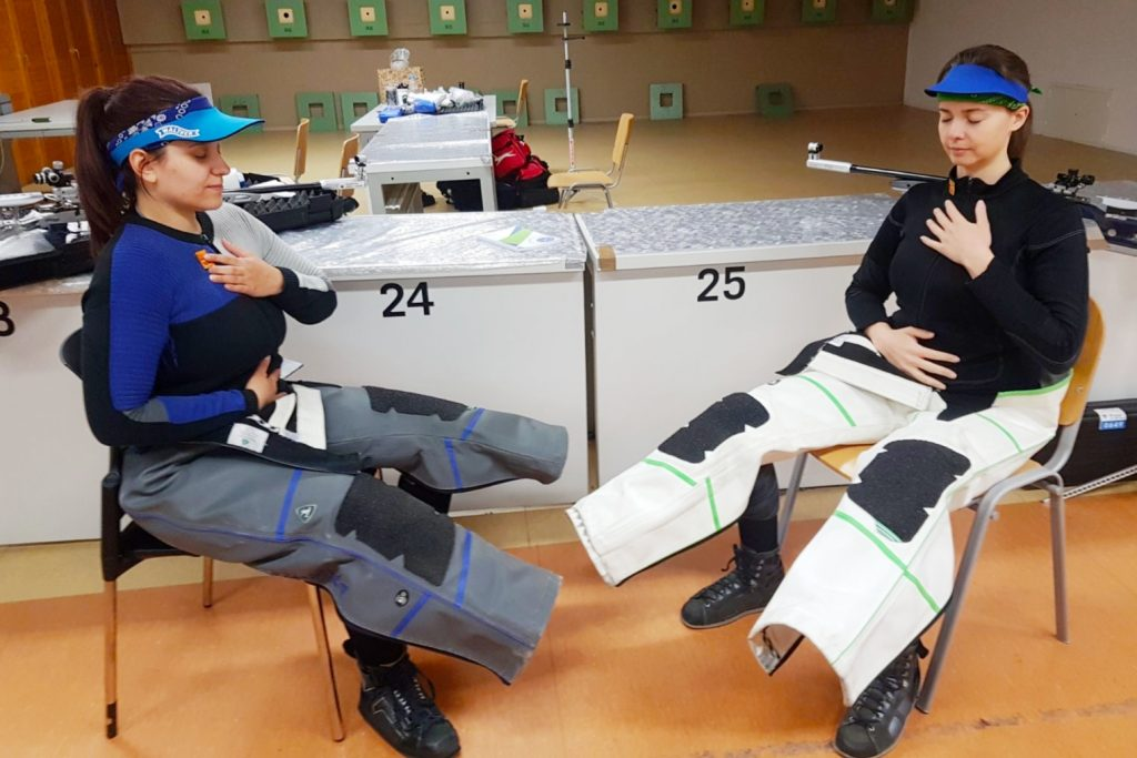 Two girls in shooting kit sitting on chairs and practicing a breathing technique